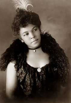 lovely young woman 1899. feather in her hair and lovely shawl and dress with cameo.