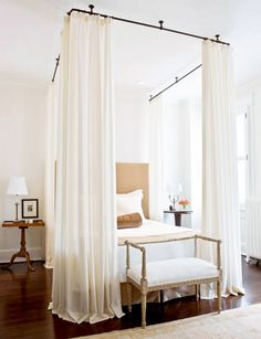 I am not the curtained- or canopied-bed type, but if I were, this would be a fun approach to take! — Elegant White Bedroom With Industrial Piping Curtain Rods