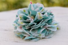 This hair clip has frayed edges & one small bead in the center. It is made with a light blue/turquoise with white flowers fabric & measures 2.5 inches. A partially lined alligator clip is attached to the back.
