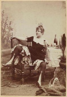 La Goulue assise sur une chaise, jambes écartées, tenant une cigarette à la main droite et un verre de vin à la main gauche. 1885