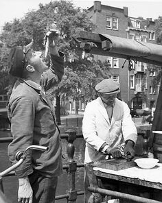 1950. Man is eating a new salt herring in Amsterdam. Photo Kees Scherer…