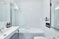 House tour: a stylish apartment with a sense of grandeur that belies its size: The apartment's minimalist bathroom with all-white subway tiles.