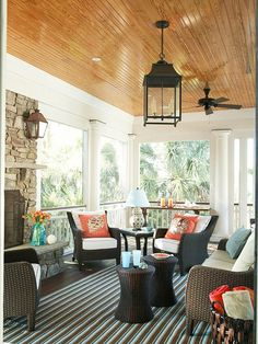 Screened porch with fireplace, bead board ceiling and lantern light fixture.