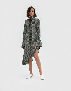 Contemporary dress from KIMHĒKIM in Black-and-White jacquard. Raised turtleneck collar. Concealed back zip closure. Exaggerated bell sleeves. Asymmetric ruffle hem. Jewel buttons. Unlined. Gently flared silhouette.  • Jacquard Weave • 90% wool, 10% nyl