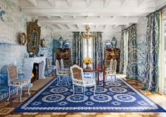 Featuring walls decorated in a tile mural by Atelier Prométhée, the dining room of a California villa designed by Juan Pablo Molyneux is furnished with a French Empire table, Louis XV–style chairs, a pair of 18th-century Chinese cabinets on stands, and a Juan Pablo Molyneux–designed rug, custom made by Tsar; the mirror is 17th-century French, and the curtains are made of a Donghia fabric.