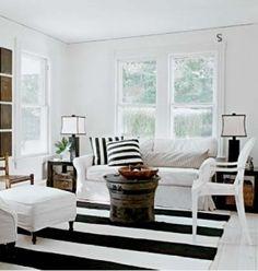 """""""A sala usa o preto e o branco, simplesmente. O ponto forte é o tapete listrado. As almofadas remetem ao tapete. Os abajures repetem o preto e branco e as paredes claras e limpas, junto com o sofá e puffs com capa branca deixam o ambiente leve e luminoso. A madeira de alguns móveis ajuda a """"aquecer"""" . Nesta combinação, quando há mais branco o ambiente fica claro e leve, quando há mais preto que branco, a tendência é ficar mais sofisticado, mas mais escuro e pode ficar opressivo em ambientes…"""
