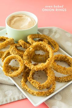 Learn how to make crispy oven baked onion rings at home. This recipe is much lower in fat than the fried restaurant version and includes a delicious savory dipping sauce too!