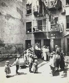 Visting Nurse instructing mothers in a tenement house back yard