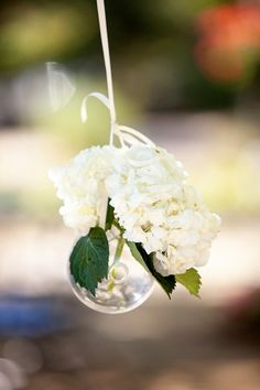 These small clear ornaments would look divine hanging from a big tree! Love the white, but maybe a different choice in flower...