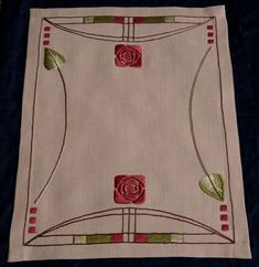 Roycroft Rose Table Scarf  $325.00  This 26-inch by 20-inch table scarf was inspired by the architectural elements of the Roycroft Inn within its amazing stained glass windows and arches, comes the Roycroft Rose Table Scarf.  Stitched on Devonshire Art Cloth in Camel (a heavyweight linen with warm coloring) using satin stitch, padded satin stitch, and stem stitch.  A double folded hem is worked along all edges; creating weight to provide a great drape.