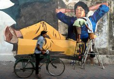 "Indian artist Ranjit Dahiya works on a mural of Bolllywood actor Amitabh Bachchan from his classic film, ""Deewar,"" in Mumbai on Wednesday. To celebrate the centennial of Indian cinema in 2013, artists from Bollywood Art Project are decorating the walls of the city in the style of classic hand-painted Bolllywood posters. Photo by Indranil Mukherjee/AFP/Getty Images."
