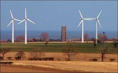 Winterton-on-Sea é uma antiga vila pesqueira em Norfolk, Inglaterra, Reino Unido. Vê-se a torre da Igreja de Martham, em Winterton, o parque eólico Somerton e mais ao fundo o Mar do Norte. Somerton é um dos primeiros parques eólicos no Reino Unido. As dez turbinas foram instaladas em 1992 e geram 2,25 megga-watts, que é suficiente para abastecer cerca de 1000 casas. As 10 turbinas estão sendo substituídas por 2 turbinas com uma potência maior do que as atuais 10.  Fotografia: Simon K. no…