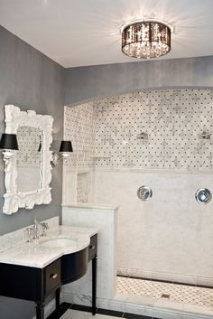Tile from the Tileshop. white carrara marble basketweave yiles shower surround, espresso stained chic vanity with white carrara marble countertop, white rocococ mirror, sconces with black shades, gray walls paint color and black pendant chandelier.