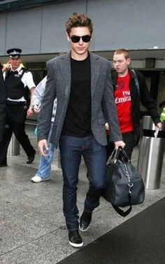 Men's Black Sunglasses, Black Crew-neck T-shirt, Charcoal Wool Blazer, Navy Jeans, Black Leather Holdall, and Black Leather High Top Sneakers
