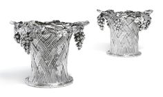 A pair of Victorian silver two-handle 'grape basket' wine coolers, Jean-Valentin Morel, London, 1851 waisted form with simulated basket-weave decoration, ribbon-tie reeded rims, stylised branch handles, the tops overflowing with fruiting vines, detachable rims and liners, the rims with engraved crest and motto