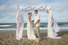 OBX beach wedding with wooden white arbor wrapped in sheer white fabric, ribbons in shades of pink.  The Embellishers in Kill Devil Hills.  #OBXWedding #BeachWedding #DestinationWedding