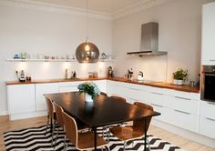 This Scandinavian kitchen is simple and minimalist. Love the decorative rug and globe pendant lighting