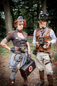 Castlefest Couple - steampunk man and woman with gadgets (woman: medic with mechanical monocle, medical supplies, hat, epaulets, gauges, etc. Man: photographer with brownie camera, gun, mechanical monocle, goggles, top hat, waistcoat) - For costume tutorials, clothing guide, fashion inspiration photo gallery, calendar of Steampunk events, & more, visit SteampunkFashionGuide.com