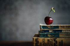 http://definitelydreaming.com/vintage-books-use/  Vintage books & a cherry on top!  Still life photography, online photography courses