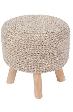 Hand-woven wool forms this charming pouf that provides comfort as a footstool or impromptu seating in a pinch, while a trio of wooden legs adds a rustic touch.
