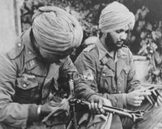 Two Sikh Waffen-SS volunteers learning to dismantle their machine gun.