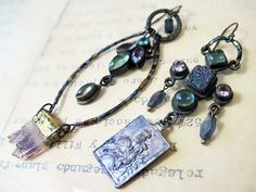 Mother of the Moon. Rustic gypsy asymmetrical by fancifuldevices, $60.00--Bits of a broken Nicki Butler necklace with a tiny amethyst slab and an antique medal colored with iridescent pigment powder.