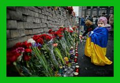 KIEV, UKRAINE - FEBRUARY 23: A young girl lays flowers left for anti-government demonstrators killed in clashes with police on February 22, ...