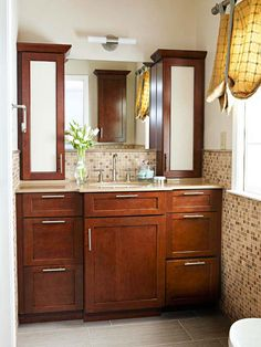 Affordable Solution-Stock kitchen cabinetry -- a combination of three base cabinets and two narrow upper cabinets -- creates loads of storage in this bathroom at a fraction of the cost of a traditional vanity.