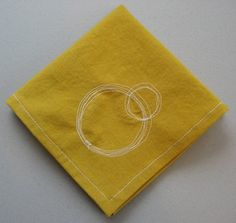 """This particular set of 4 napkins is mustard yellow with white contrasting stitching. The corners are all beautifully mitered and each are embellished with a circle stitch as shown. They measure 10"""" square. $10"""