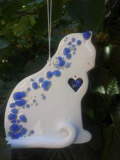Adoro sperimentare!!!!Questo è il mio primo esperimento ceramica/vetro....Ho utilizzato i cocci di un vaso di vetro blu opportunamente tritati e cosparsi sul micio maiolicato. Una volta cotto ho contornato ogni singola fusione di vetro con color argento e ho impreziosito il gatto con un cuoricino di cristallo color zaffiro ehhh per finire....ho inserito delle belle vibrisse!!