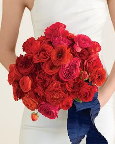 Bouquet with Red Roses and Ranunculus    This voluptuous clutch of riotous red roses and ranunculus is the bright color of kissable lips. Forgo the expected swath of smooth satin, and gather them together in a crisp, box-pleated ribbon instead.