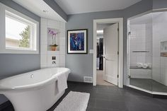 Soft gray paint color in this modern, large bathroom design with a unique standalone bathtub, slate gray flooring and white trim.