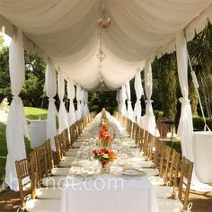 The dinner took place under a tent, which was dramatically dressed with chandeliers and flowing curtains. Instead of several small tables, one long banquet table was set with Melissa and Stuart at the head -- literally everyone was sitting at the bride an...