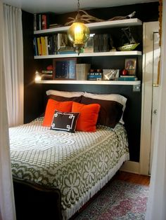 Small bedroom with no room for a nightstand has dark walls, a hanging light and shelves above the bed.