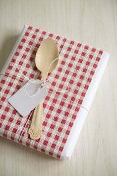 Gift wrap inspiration -- use a tea towel and a spoon to wrap a cookbook!