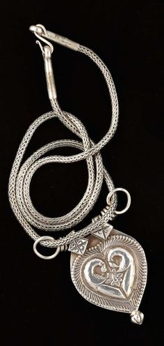 India |  Silver pendant in the shape of a heart decorated with two peacocks.