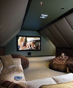 A pair of ceiling speakers for surround sound, a projector and a comfy sectional, and it's family movie night every night. Amazing attic idea.