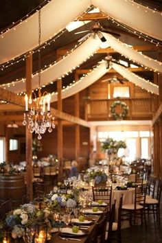 A simple chandelier and strung up lights add so much to this rustic barn! {Anne Robert Photography}