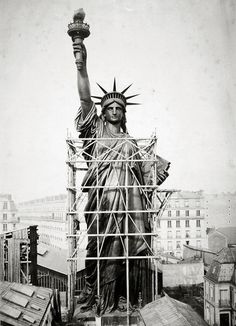 The Statue of Liberty looms over Paris surrounded by scaffolding as workers complete the final stages of construction. 1884.