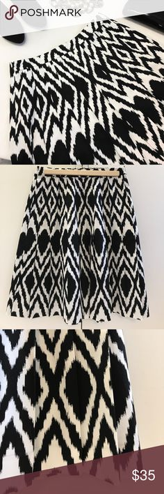 """Talbots Black & White Pleated Skirt This pleated skirt by Talbots makes a bold statement in a graphic black & white print.  The skirt has a band at the waist with a hidden zipper on the left side.  The entire skirt is pleated for a formal, structured look.  The skirt is designed to hit at the knee.  It is made of 98% cotton & 2% spandex so it will wash & wear great!  Measured laying flat:  waistband 14"""" across; hip area approx. 20"""" across; length to hem approx. 22"""".  In like-new condition…"""