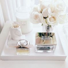 This bathroom tray is beautifully styled and shows off a pretty perfume bottle, candle and a small bouquet of roses - but is also functional holding a storage box and container with q-tips. For a simple and cohesive look, stick to one neutral color such as black, white or gray.