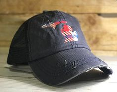 Blue distressed trucker hat with plaid Michigan silhouette.