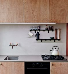Plywood cabinets and reconstituted stone counter in a small kitchen by London architect Simon Astridge