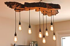 RUSTIC/ EARTHY/ SCULPTURAL ** This piece is ready to ship when you are. ** Extreme live edge wood slab base 44x24 with 8 free hanging Edison bulbs. This funky shaped live edge Olive wood slab with antique fabric wire and Edison bulbs will be the focal point of any room. Looks
