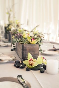 Flowers, succulents and smooth rocks make a lovely, organic wedding centerpiece.