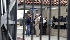 San Diego police officers and federal agents occupy the gate to the Point Loma Naval facility in San Diego Thursday Feb. 7, 2013 during a manhunt for former Los Angeles officer Christopher Dorner in San Diego.