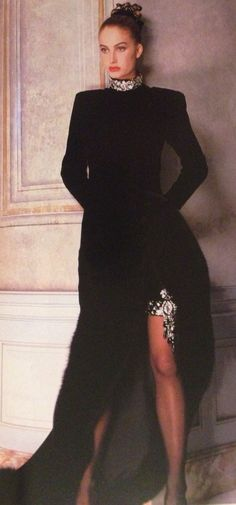 Pierre Balmain Haute Couture- A/W 1987-88 Long black velvet gown dress with a high slit, underlined with a fox fur border that reveals shorts adorned with a rhinestone garter embroidered by Lanel, with rhinestones around the neck. L'Officiel No. 734- September 1987