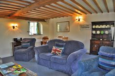 The spacious lounge has two arm chairs and a two seat sofa, facing the the large inglenook fireplace, filled with candles, (no open fires).             #Cotswolds #luxury #holiday #rental