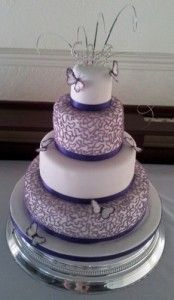 "Lilac filigree, purple ""ribbon"" an butterfly wedding cake. The butterflies are made from hand painted feathers."
