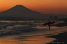 photo by Takayuki Miyamoto A surfer in the sunset at Shonan, Kugenuma beach in Japan.